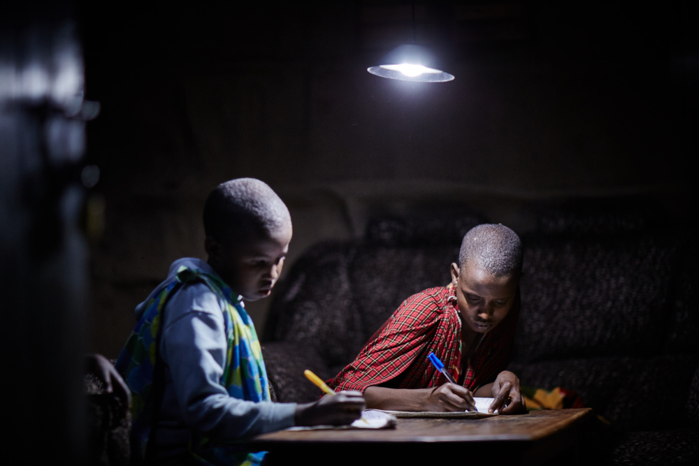 Two boys working under a lamp